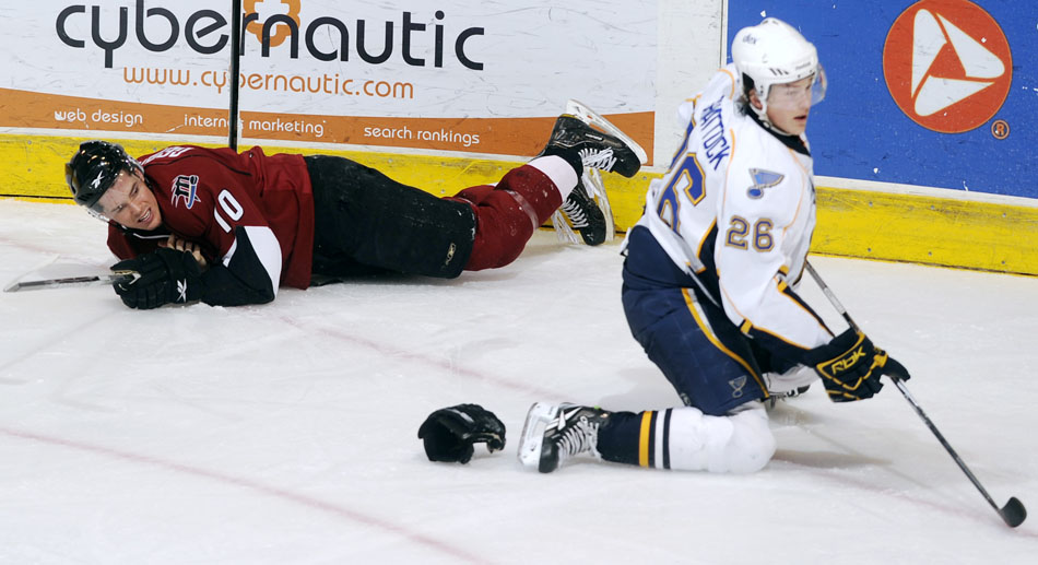 Lake Erie Monsters defender Matt Generous (10) lays on the ice after a hit from Peoria Rivermen right wing Tyler Shattock (26) during a game on Sunday, Dec. 19, 2010, at Carver Arena.