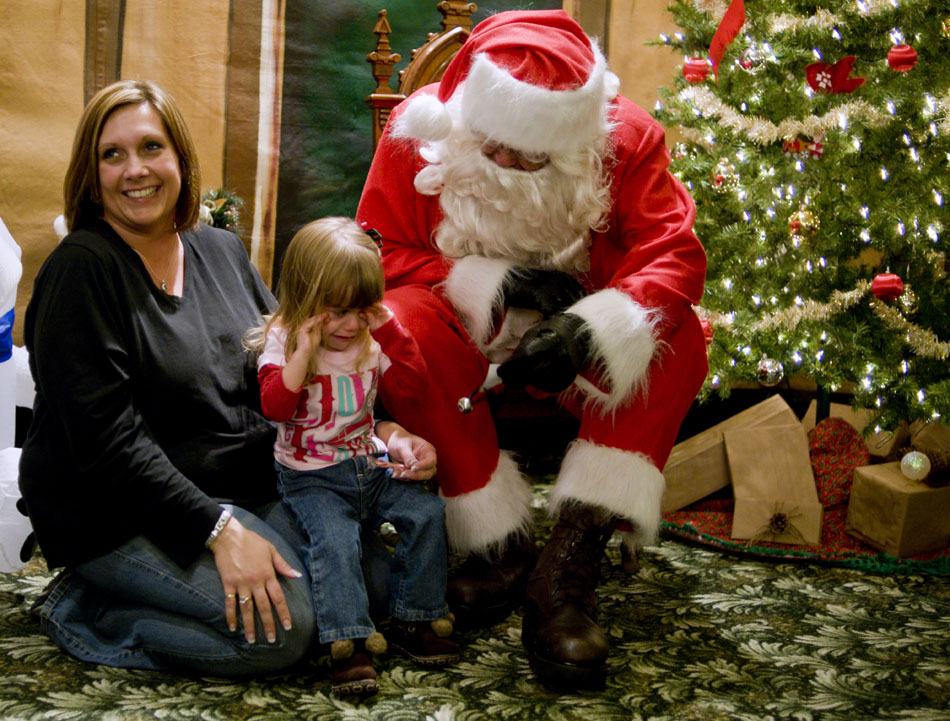 Cheri Crebo, left, can only smile as her daughter, Ava, age 2, cries after meeting Santa Claus on Friday, Dec. 10, 2010, at Wildlife Prairie State Park. Crebo vowed to get back in line a second time to see if Ava would sit on Santa's lap.