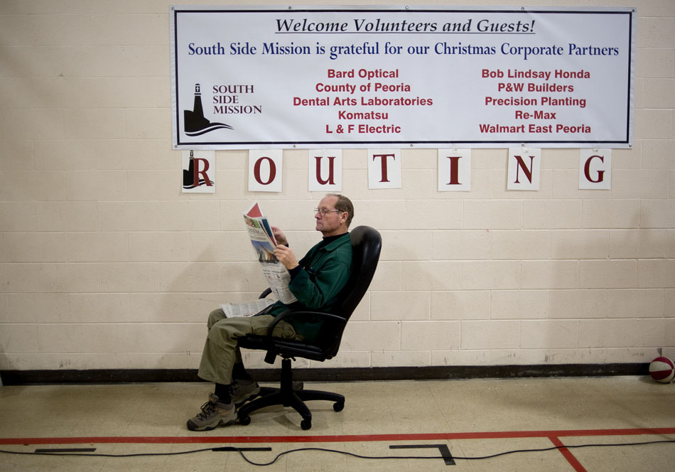 Steven Johnston, of Farmington, relaxes as he reads a Journal Star before the start  of a in-house Christmas meal on Saturday, Dec. 25, 2010, at the South Side Mission.