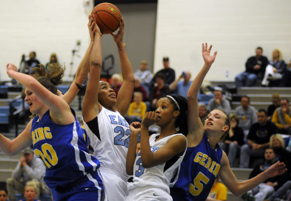 East's Brittany Lawson (22) grabs a rebound in traffic in front of teammate Destiny Rudolph (3) and Gering defenders Jordan Plummer (20) and Morgan Greene  (5) during a game on Thursday, Jan. 13, 2011, at East.