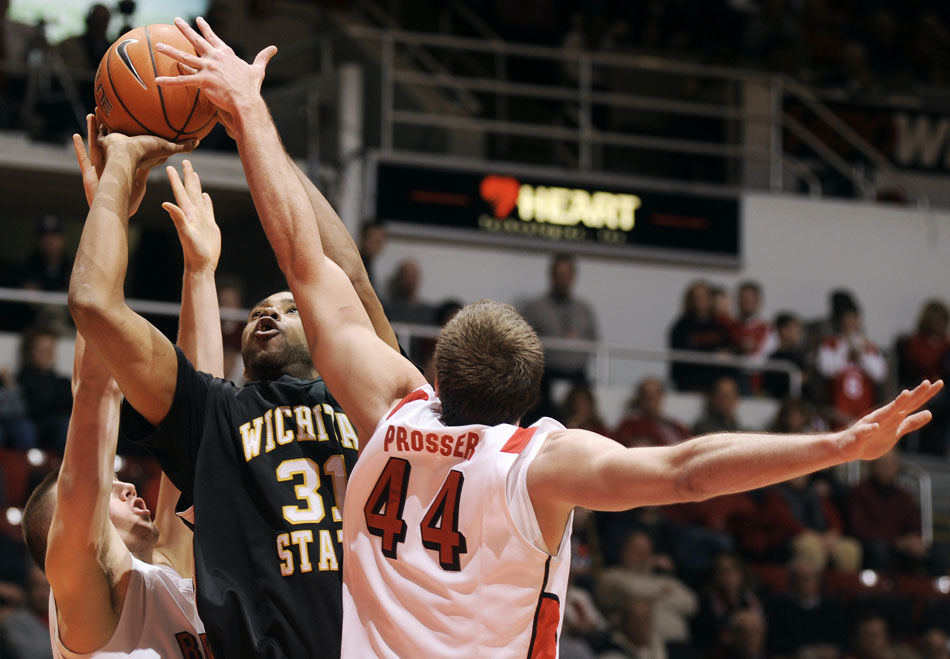 Wichita State forward/center J.T. Durley (31) puts up a shot in front of Bradley forward Jordan Prosser (44) and guard Jake Eastman during a game on Saturday, Jan. 1, 2011, at Carver Arena in Peoria, Ill.