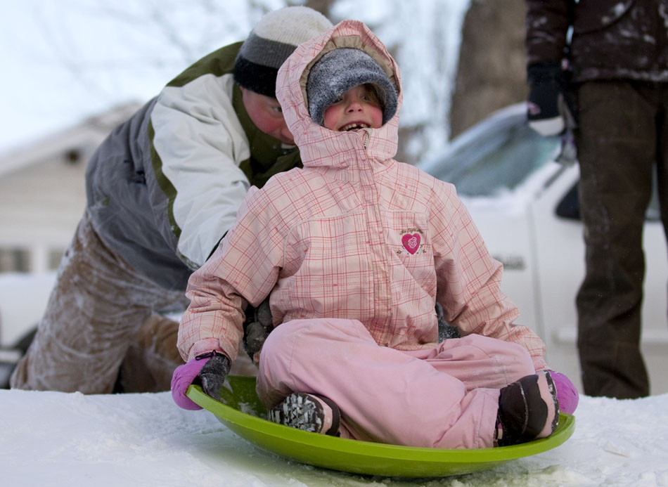 Sky Bluemer, age 7, reacts after getting a starting shove from her dad, Tyler, sending her sledding down a hill on Tuesday, Feb. 8, 2011, at Pando Park in Cheyenne. A fresh snowfall attracted a few folks to the park with their sleds.