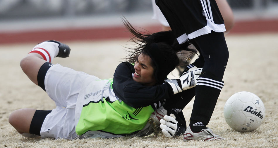 Cheyenne South goalie Oxsanna Beltran hangs on to the leg of Cheyenne East's Anna Kingston to prevent Kingston from scoring during a girl's soccer junior varsity game on Thursday, March 17, 2011, at Cheyenne South High School. Kingston scored and Beltran was injured on the play.