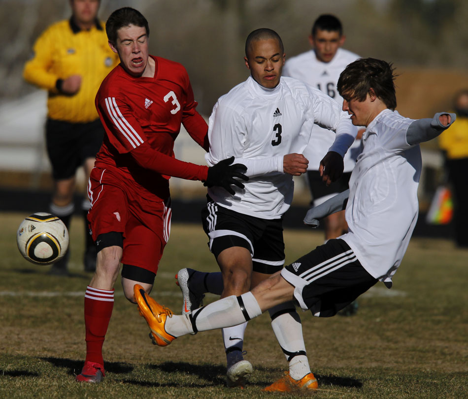Scottsbluff's Shane Weyrich (3) reacts as Cheyenne East's Clay Casey (13) kicks the ball away on defense with teammate Raz Lavalais, middle, during a boy's soccer game on Tuesday, March 22, 2011, at Cheyenne East High School.
