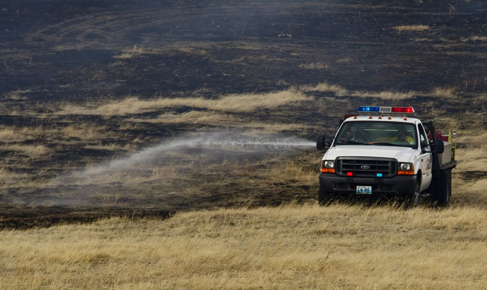 Laramie County fire fighters work to extinguish a few hotspots after a brush fire on Friday, April 1, 2011, in a field near County Road 128 north of Cheyenne. The fire burned several acres of land before fire fighters brought it under control.