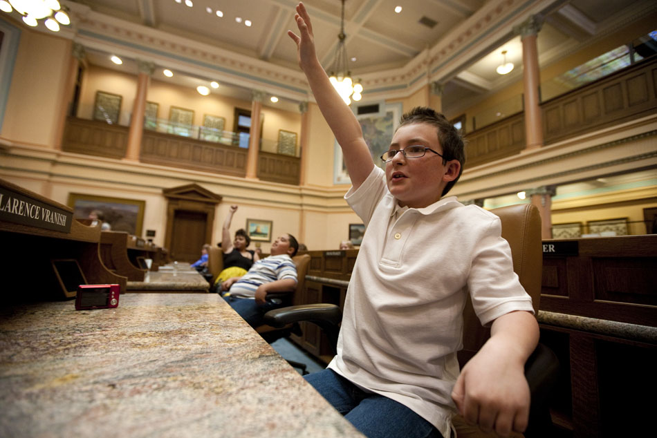 Tanner Bucklen-Lindgren, a fifth grader at Arp Elementary, raises his hand as he waits to be called so he can debate an amendment to a mock bill dealing with a teacher dress code on Tuesday, April 26, 2011, on the floor of the House chambers in the Wyoming State Capitol.