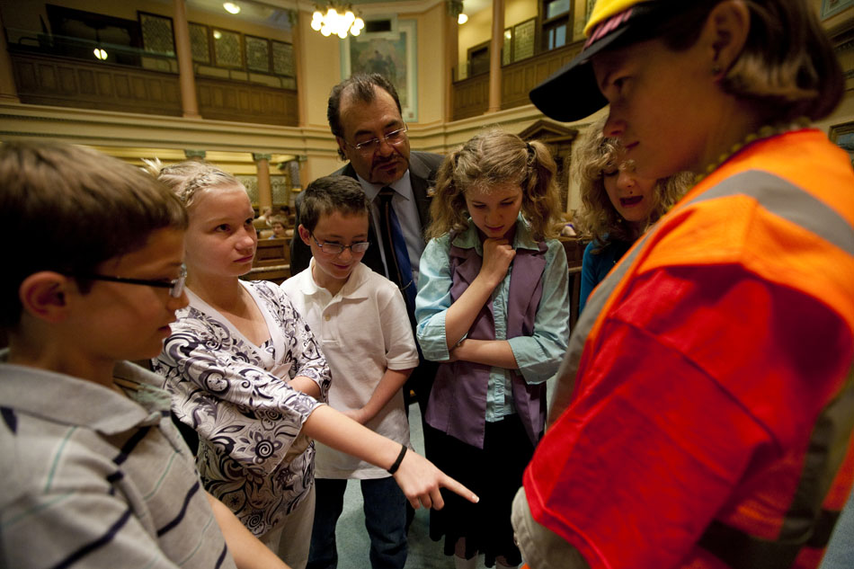 Micaela Heigis, left, points to a belt that she didn't like as part of Katie Mugg's outfit as a conference committee of fifth graders from Arp Elementary debate a bill dress code for teachers on Tuesday, April 26, 2011, on the floor of the House chambers in the Wyoming State Capitol. The youngsters passed a dress code for Mugg, a tutor at the school, and each change represented an amendment to the bill. The overall dress coded failed to pass because the fifth graders on the House side didn't like Mugg's orange safety vest.