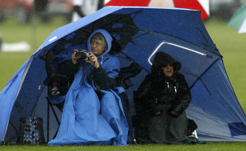 A fan looks to take a picture of the action from under an umbrella during a Class 4A boy's state soccer game on Friday, May 20, 2011, in Sheridan, Wyo.