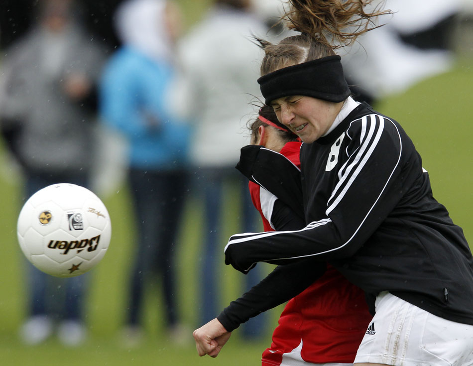 Cheyenne East's Sara Erickson, right, reacts after colliding with a Cheyenne Central player while competing for a header during a Class 4A girl's state soccer third place game on Saturday, May 21, 2011, in Sheridan, Wyo.