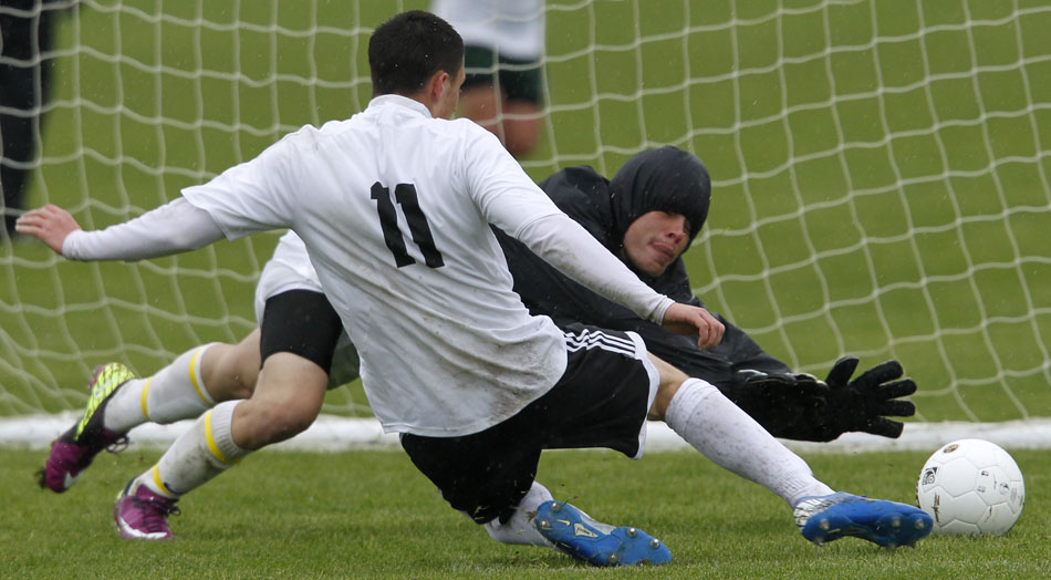Cheyenne East's Trey Herrera (11) slides in to put a shot on goal as Green Rivers keeper Kenyon Baker dives to make the save during a Class 4A boy's state soccer fifth place game on Saturday, May 21, 2011, in Sheridan, Wyo.