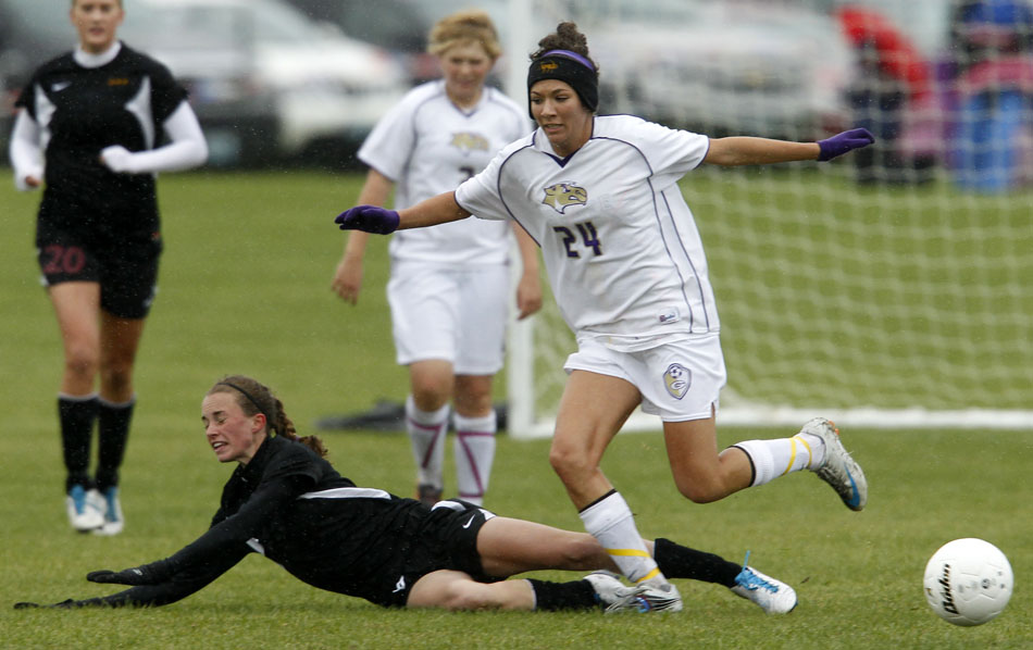 Laramie's Megan Dooley, left, falls to the pitch after drawing contact from Gillette's Michelle McGeary during the Class 4A girl's state soccer championship game on Saturday, May 21, 2011, in Sheridan, Wyo.