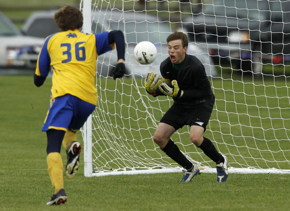 Laramie keeper Andrew Amen makes a save in front of Sheridan's Andrew Slikker (36) during the Class 4A boy's state soccer championship game on Saturday, May 21, 2011, in Sheridan, Wyo.