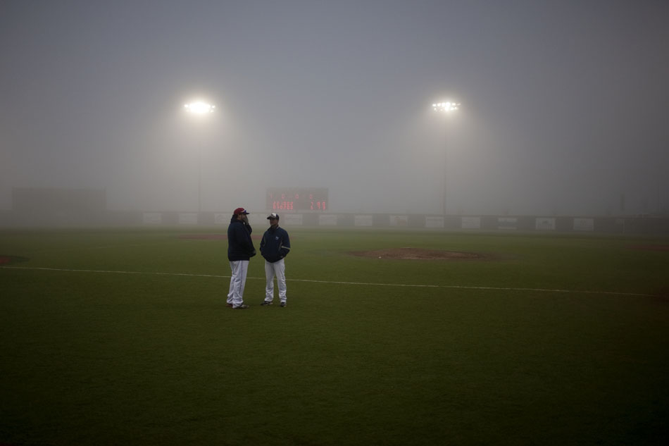 Coaches talk on the field during a fog delay on Sunday, May 29, 2011, at Powers Field in Cheyenne. The fog blanketed the outfield making it hard to see pop ups, forcing officials to postpone a game between Cheyenne Post 6 and Ralston Valley until 9 a.m. on Monday.