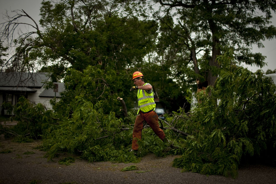 Edward Cullen, a City of Cheyenne employee, puts his arm up as he hops over a downed tree limb on Thursday, June 30, 2011, along House Avenue between Sixth and Seventh streets on the city's southeast side. Cheyenne spent part of the evening under a severe thunderstorm warning as rain and high winds swept across the area.