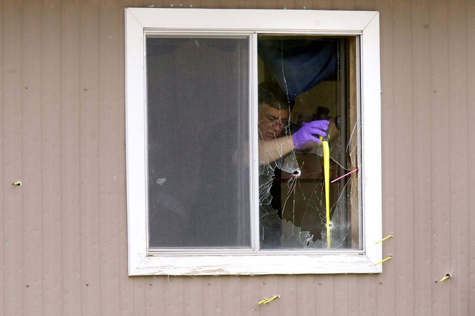 A crime scene technician takes a measurement in a window of a mobile home that appears to have been broken by a bullet on Friday, July 8, 2011, at 757 E. Oak St. #19 in Wheatland, Wyo. Wheatland police arrested Everett Conant III at the home Thursday evening after a shooting that left four people dead and one injured. The yellow and magenta sticks protruding from the building are commonly used to determine bullet trajectories in crime scene investigations.
