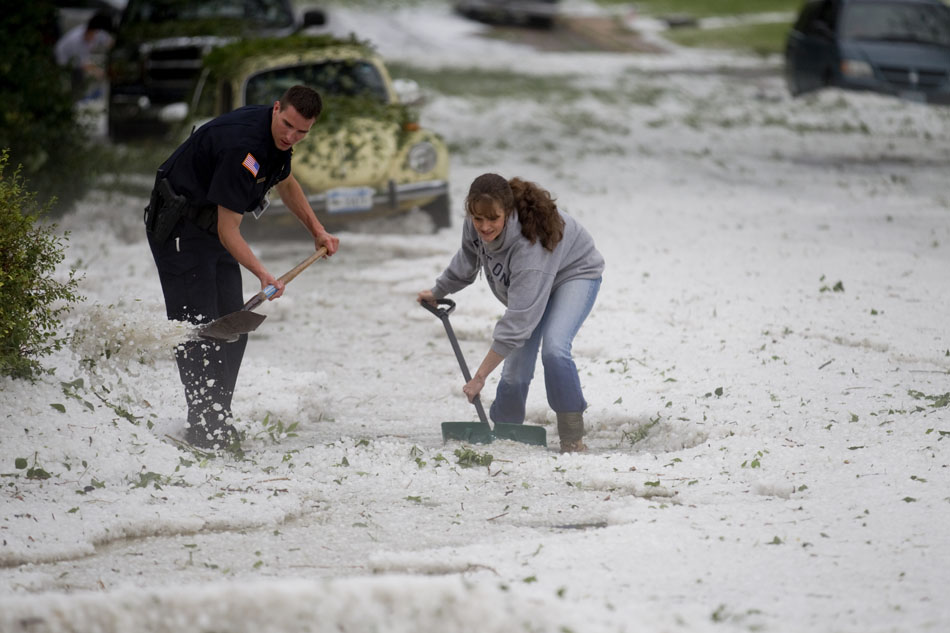 "Cheyenne police officer Joel Hickerson, left, and Christine Escobar shove debris out of a storm drain on Tuesday, July 12, 2011, at the intersection of 23rd Street and Bradley Avenue in Cheyenne. Escobar, who lives one house from the intersection on 23rd Street, said she was able to save a few things in her basement before a ""waterfall"" flooded her home. Several residents, police officers and city employees armed with shovels, pitch forks, brooms and military entrenching tools quickly cleared debris from the intersection's drains to allow flood waters to subside until a city snow plow and two front loaders arrived to clear the intersection."