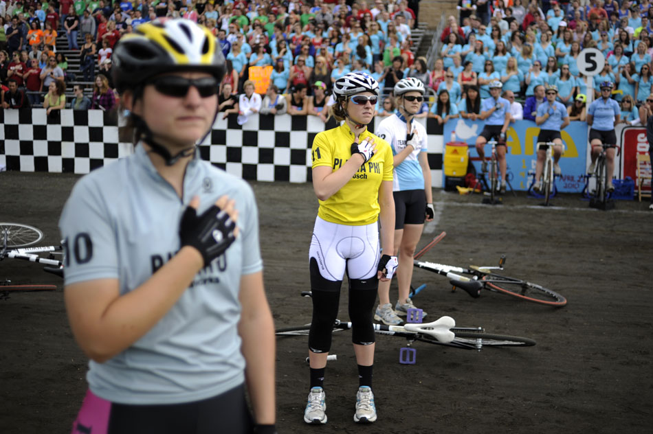 Phi Beta Phi rider Caroline Brown, middle, watches an American flag wave during the playing of the National Anthem before the start of the Women's Little 500 on Friday, April 23, 2010, at Bill Armstrong Stadium. (James Brosher/Bloomington Herald-Times)