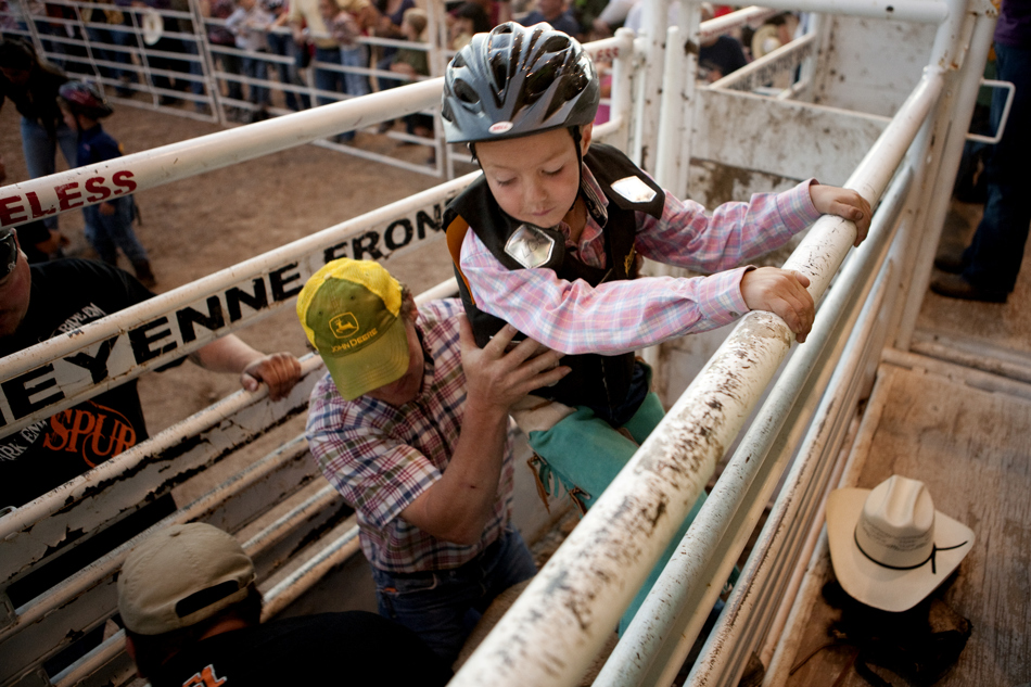 Karrol Brennecke, 8, eases his way down into a chute for the mutton bustin during the Laramie County Fair on Wednesday, Aug. 10, 2011, at Frontier Park.