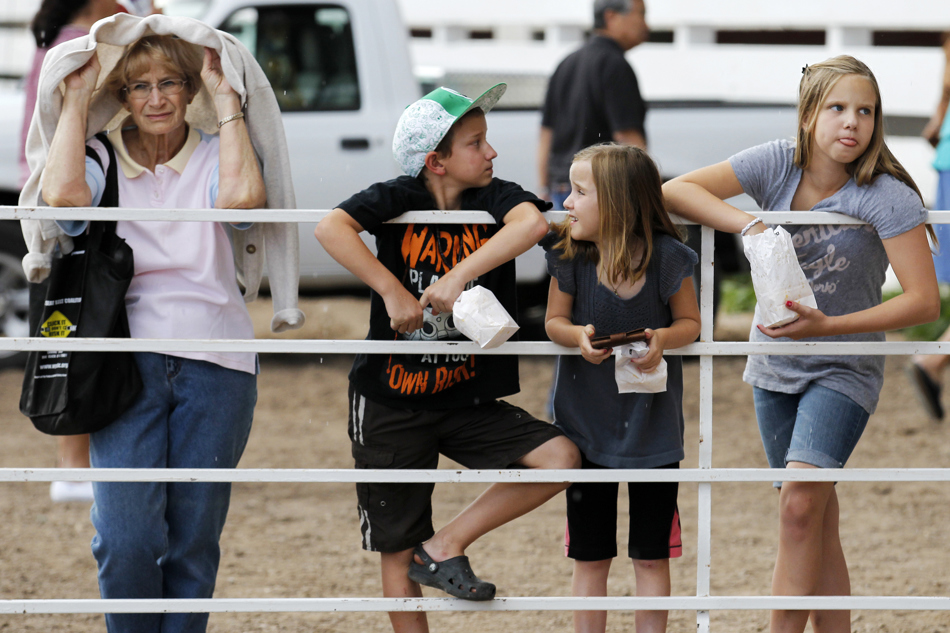 Jackie Cushing, left, covers up to stay dry in a sudden rain shower as she wais for the start of the mutton bustin with her grandchildren Ethan, 10, Lauren, 8, and Maren French, 11, during the Laramie County Fair on Wednesday, Aug. 10, 2011, at Frontier Park.