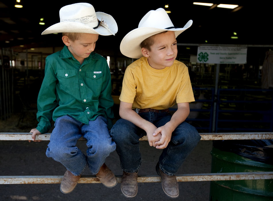 Kelton Krakow, 6, left and Cooper Lakin, 6, sit on a fence in the sheep barn during the Laramie County Fair on Saturday, Aug. 13, 2011, at Frontier Park.