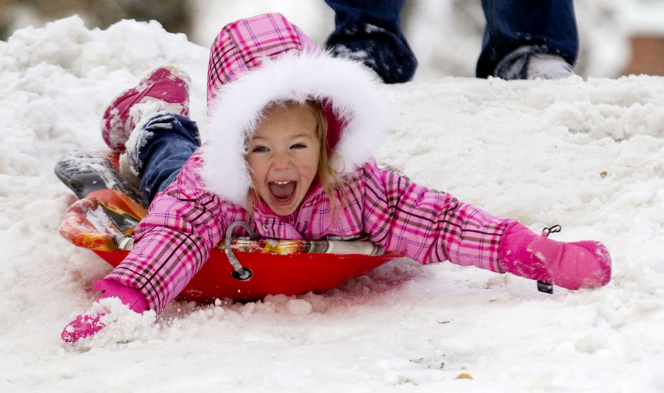 Taylor Hollibough, 3, reacts as she slides down a hill into Pando Park on Wednesday, Oct. 26, 2011, in Cheyenne. It was the first time Hollibough had sledded by herself on her own sled.
