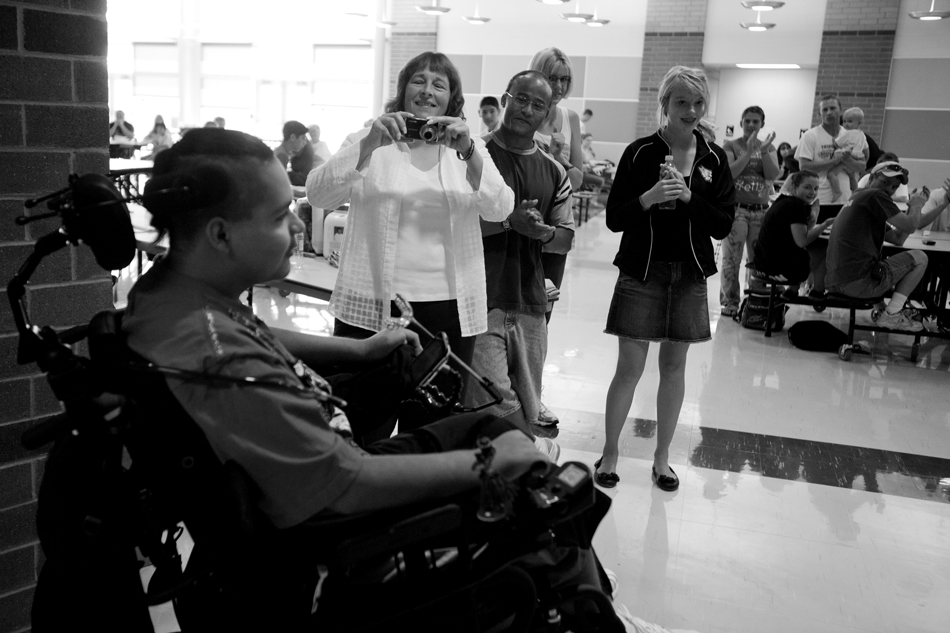 Maria Baca takes a quick snapshot of Isaac Salas as Salas rolls into a welcome home party on Saturday, Aug. 20, 2011, at Cheyenne South High School. Maria, who did not know Isaac or his family before his injury, became a quick friend of the family after she organized several charity events to raise money for his recovery. (James Brosher/Wyoming Tribune Eagle)