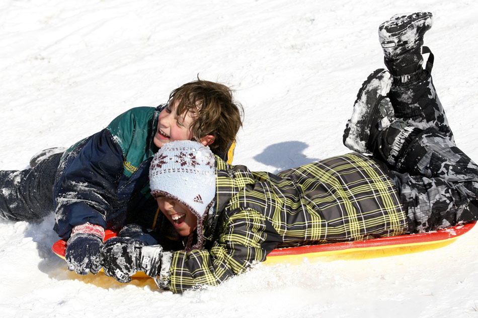 Max Grove, left, 10, and Simon Lozano, 11, react as they sled down an hill into Pando Park on Saturday, Dec. 3, 2011, in Cheyenne. Several youngsters took to the park for sledding on the fresh powder on Saturday after a Friday night snowfall.