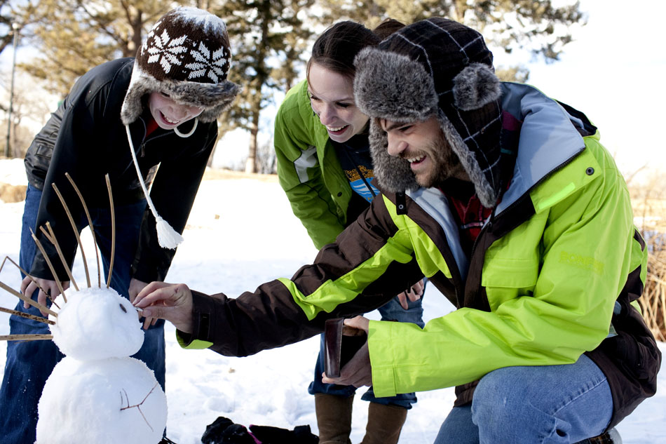Joe Melia, left, Julia Melia and Stephen Saxer put the finishing touches on a snowman complete with a Mohawk on Tuesday, Dec. 27, 2011, on a frozen pond in Lion's Park. The snowman cost a total of 27 cents to construct: two pennies for the eyes and a quarter for the nose. (James Brosher/Wyoming Tribune Eagle)