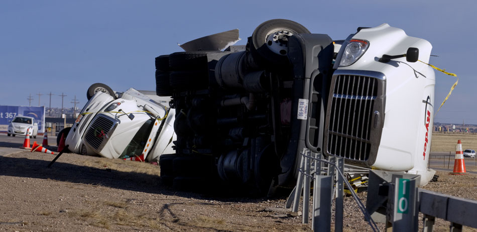 Motorists proceed cautiously past two overturned tractor trailers that were blown over by high winds on Thursday, Dec. 29, 2011, in the southbound lane of Interstate 25 just south of the High Plains interchange near Cheyenne. Wind blew over the tractor trailer pictured at right around midday on Wednesday followed by a similar incident that toppled the tractor trailer pictured in the background sometime on Thursday morning. For the second day in a row, road signs on the interstate indicated a light trailer restriction for high profile vehicles between the Colorado state line and Cheyenne due to wind gusts higher than 65 mph. (James Brosher/Wyoming Tribune Eagle)
