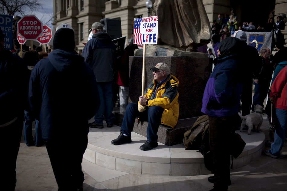 A man sits at the base of an Esther Hobart Morris statue outside of the Wyoming State Capitol during an anti-abortion rally and march on Saturday, Jan. 21, 2012, in Cheyenne. (James Brosher/Wyoming Tribune Eagle)