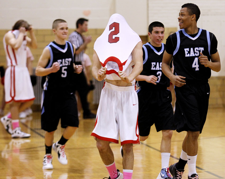 Cheyenne Central's Kyler Robinson (2) pulls his jersey off in frustration after a desperation three pointer at the buzzer drew iron as Cheyenne East players Treyven Gallegos (4), Cameron Jaure (3) and Cameron Johnson (5) celebrate on Saturday, Jan. 21, 2012, at Storey Gym in Cheyenne. (James Brosher/Wyoming Tribune Eagle)