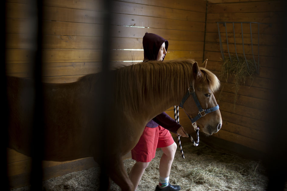 April Boughton moves a 4-year-old horse named Beauty back to her stall as Boughton works in the stables on Friday, April 20, 2012, at Hannah and Friends in South Bend. Boughton, 22, comes to stables to groom the horses once a week. (James Brosher/South Bend Tribune)