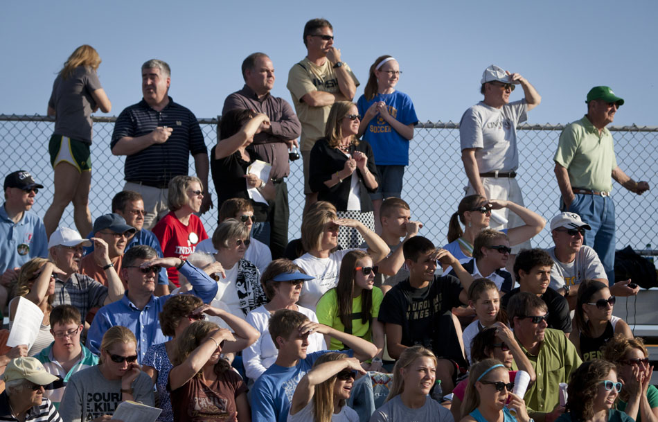 Parents and fans shade their eyes from the sun as they look westward to watch a relay final from the stands during the Bremen girl's track and field sectionals on Tuesday, May 15, 2012, at Bremen High School. (James Brosher/South Bend Tribune)