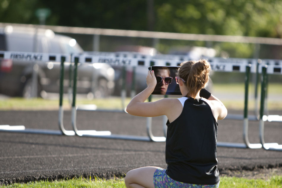 A spectator uses an iPad to photograph a hurdles event during the Bremen girl's track and field sectionals on Tuesday, May 15, 2012, at Bremen High School. (James Brosher/South Bend Tribune)