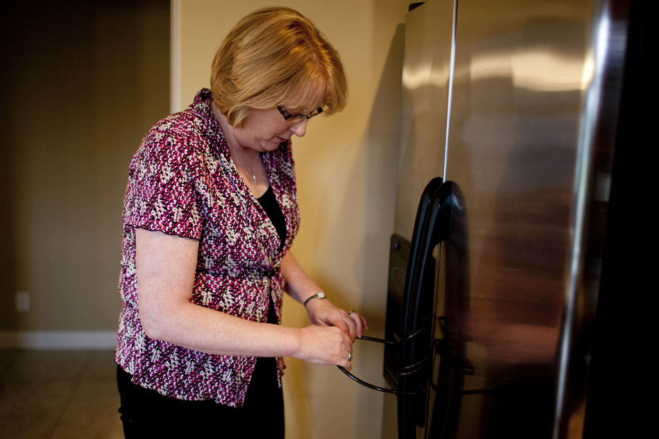 Debbie McKissick unlocks her refrigerator as she prepares to warm up dinner for her son, Greg Gaver, not pictured, on Wednesday, April 25, 2012, at their family home in Granger. Gaver, 21, suffers from Prader-Willi Syndrome which in part gives him an intense craving for food, promoting his parents to keep food in their home locked. (James Brosher/South Bend Tribune)