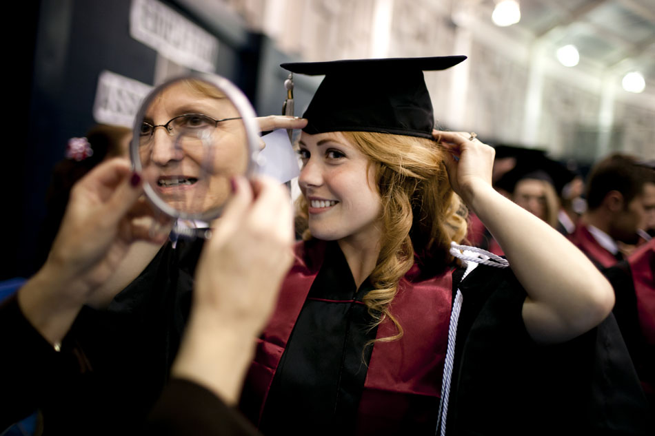 Kelsey Cramer carefully adjusts her cap with some help from Brenda Bickel, a member of the IU-South Bend General Studies alumni board, reflected in mirror, before the Indiana University-South Bend commencement exercises on Tuesday, May 8, 2012, in the Purcell Pavilion at Notre Dame. (James Brosher/South Bend Tribune)
