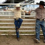 Jack Osborn, left, 10, and Brayden Wiesen, 11, take a break towards the end of the day inside of a chute during the first go of slack tie-down roping on Wednesday, July 20, 2011, at Frontier Park. Several youngsters including the two funneled cattle into chute 9 from 8 a.m. to about noon for slack tie-down roping. (James Brosher/Wyoming Tribune Eagle)