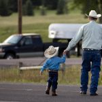 A man crosses the road with his youngster after a chuckwagon breakfast before the Cheyenne Frontier Days cattle drive on Sunday, July 17, 2011, in Cheyenne. (James Brosher/Wyoming Tribune Eagle)