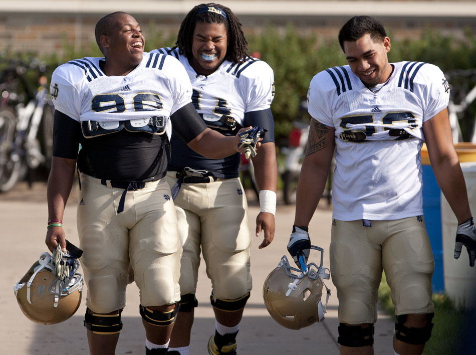 Notre Dame nose guard Tyler Stockton, left, linebacker Ishaq Williams and defensive end Justin Utupo share a laugh as they make their way across the street from the Guglielmino Athletics Complex to the LaBar Practice Fields before a practice on Wednesday, Aug. 8, 2012, at Notre Dame. (James Brosher/South Bend Tribune)