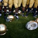 Golden helmets sit on the turf as players sing the alma mater during a NCAA college football game on Saturday, Sept. 8, 2012, at Notre Dame. (James Brosher/South Bend Tribune)