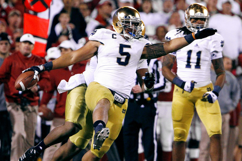 Notre Dame linebacker Manti Te'o (5) celebrates with teammates after he intercepted a pass from Oklahoma quarterback Landry Jones in the fourth quarter of an NCAA college football game on Saturday, Oct. 27, 2012, in Norman, Okla. (James Brosher/South Bend Tribune)