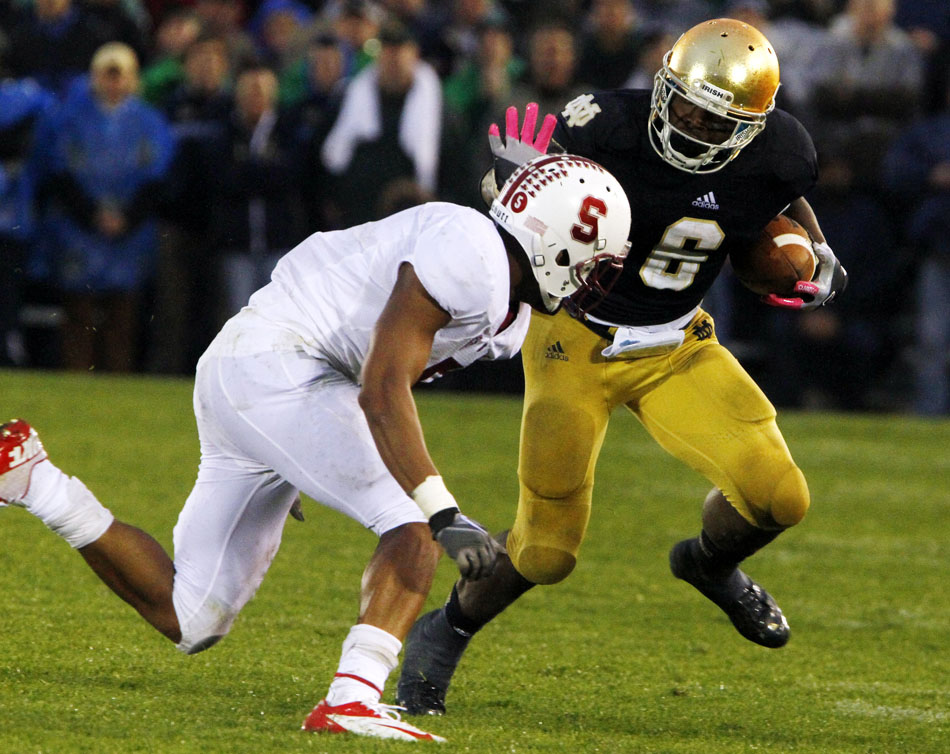 Notre Dame running back Theo Riddick (6) tries to evade Stanford safety Devon Carrington during a NCAA college football game on Saturday, Oct. 13, 2012, at Notre Dame. (James Brosher/South Bend Tribune)