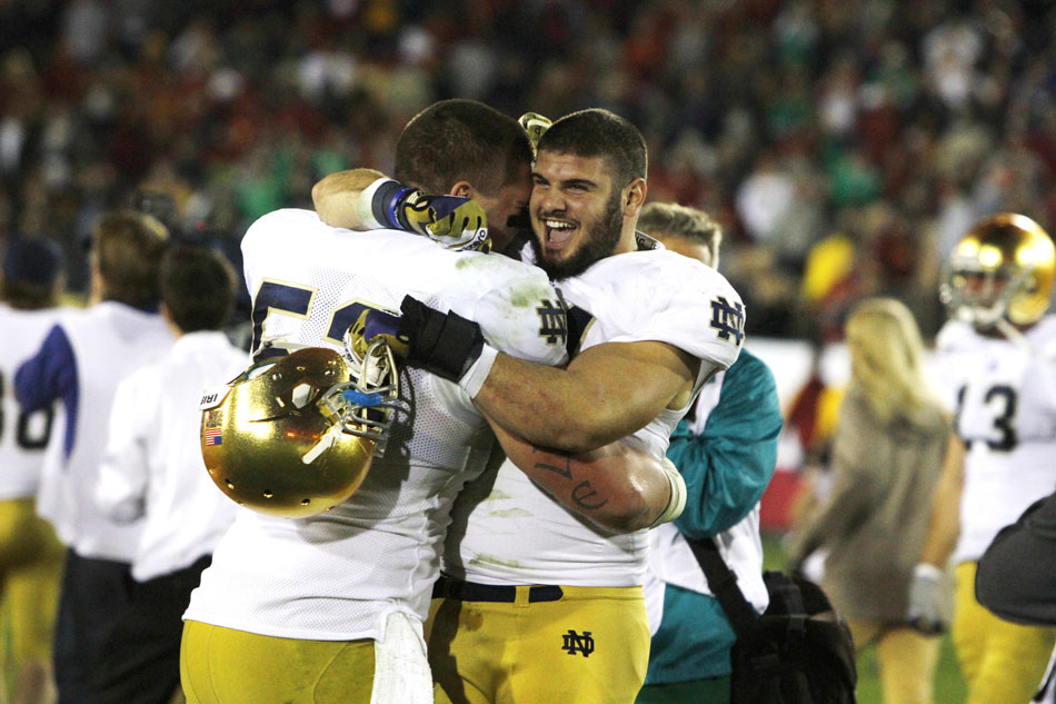 Notre Dame linebacker Carlo Calabrese celebrates with teammate center Braxston Cave, left, after a 22-13 win against USC on Saturday, Nov. 24, 2012, at the Los Angeles Memorial Coliseum. (James Brosher/South Bend Tribune)