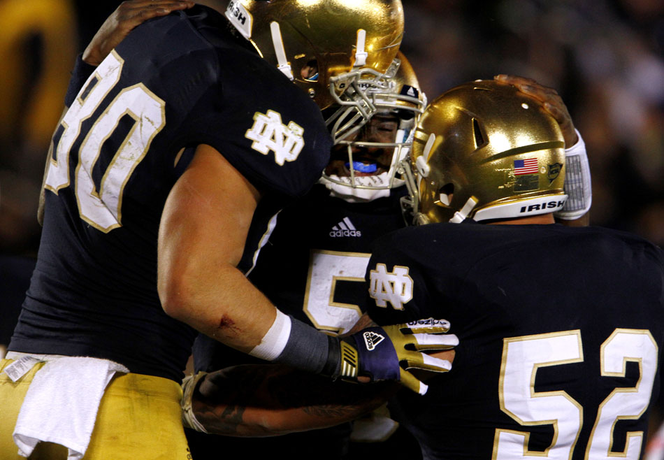 Notre Dame tight end Tyler Eifert (80) and center Braxston Cave (52) celebrate quarterback Everett Golson after Golson scored a two-point conversion to tie the game at 20 during an NCAA college football game on Saturday, Nov. 3, 2012, at Notre Dame. (James Brosher/South Bend Tribune)