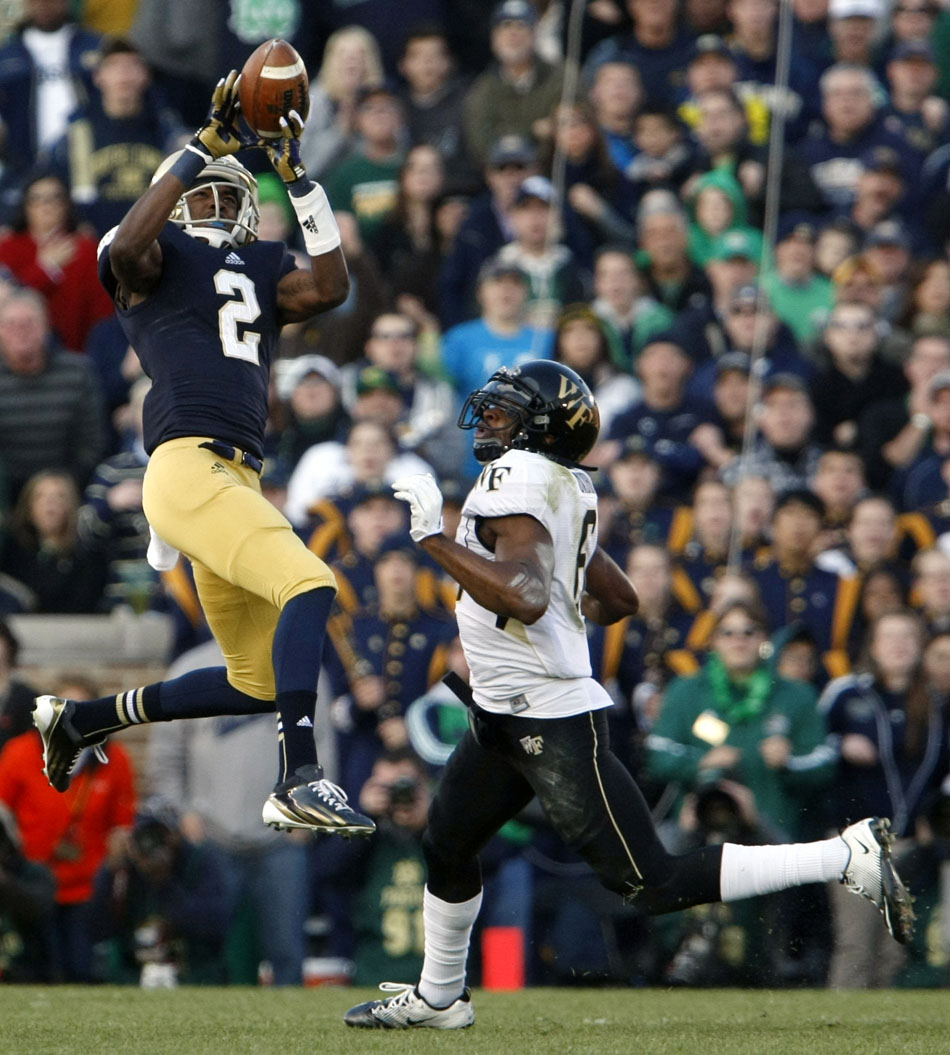 The ball hits the fingertips of Notre Dame wide receiver Chris Brown (2) in front of defense by Wake Forest cornerback Chibuikem Okoro (6) during an NCAA college football game on Saturday, Nov. 17, 2012, at Notre Dame. (James Brosher/South Bend Tribune)