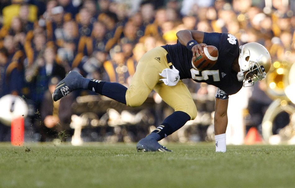 Notre Dame quarterback Everett Golson (5) stumbles in the backfield as he rolls out off of a play action fake during an NCAA college football game on Saturday, Nov. 17, 2012, at Notre Dame. (James Brosher/South Bend Tribune)