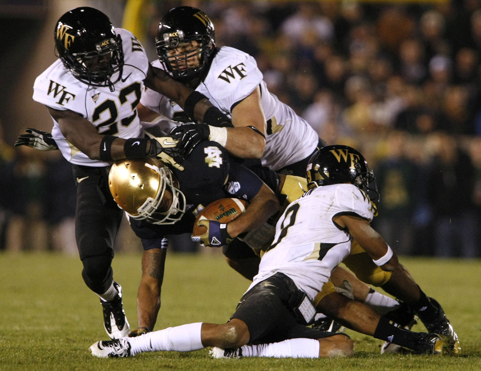 Wake Forest defenders tackle Notre Dame running back George Atkinson III (4) during an NCAA college football game on Saturday, Nov. 17, 2012, at Notre Dame. (James Brosher/South Bend Tribune)