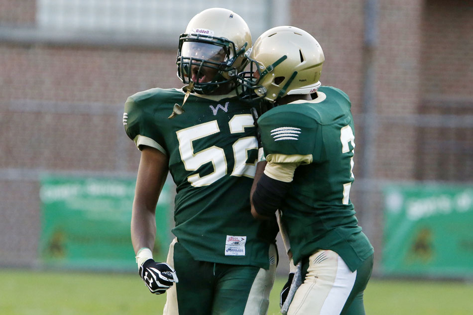 Washington's Amani Lee (52) celebrates a defensive stop with teammate Anthony Brazier (3) during a high school football game on Friday, Sept. 6, 2013, at School Field in South Bend. (James Brosher/South Bend Tribune)