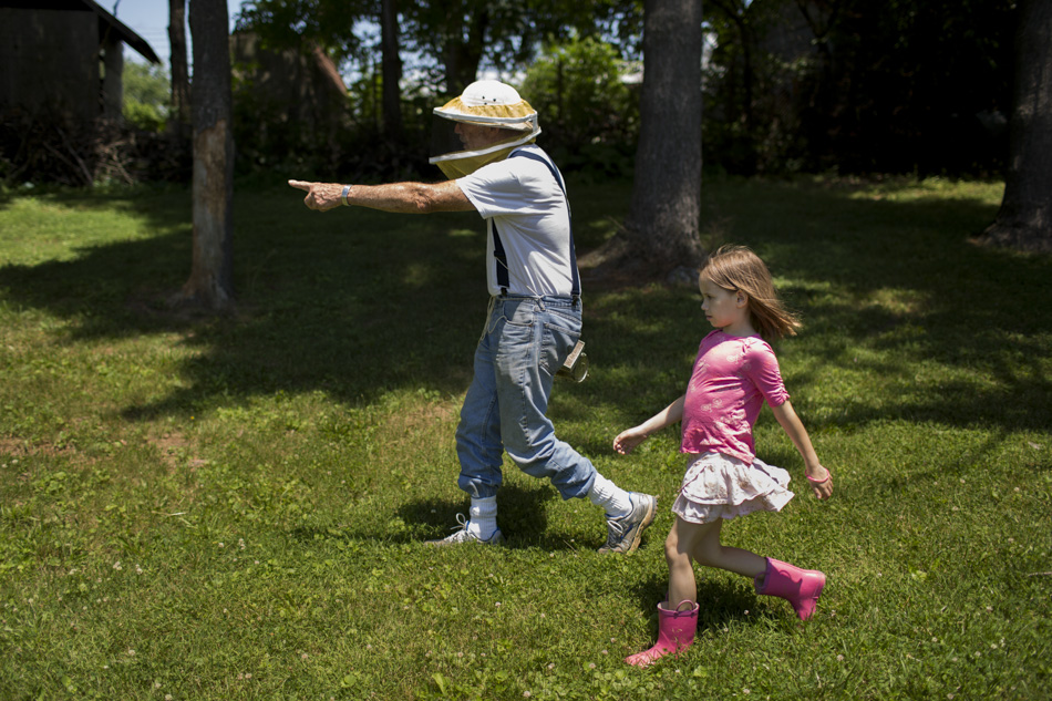 George Hegeman, an IU Professor Emeritus of Biology, leads Aurora Webeck, 7, to a beehive as he teaches her and other children, not pictured, about bees on Wednesday, June 10, 2015, at the Hilltop Garden and Nature Center. (James Brosher/IU Communications)