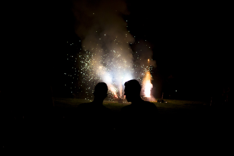 Party goers watch as a synchronized fireworks show in a backyard during the Annual Cruise on Land Summer Party on Saturday, July 25, 2015, in Bloomington, Indiana. (Photo by James Brosher)